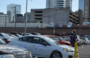 Volunteer directs cars in parking lot gathering place in Denver. Liberation photo.