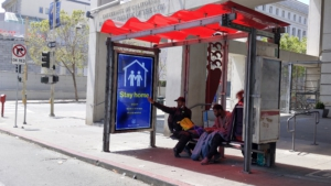 Unhoused people in bus shelter respond the the Cancel the Rents caravan in SF. Liberation photo.